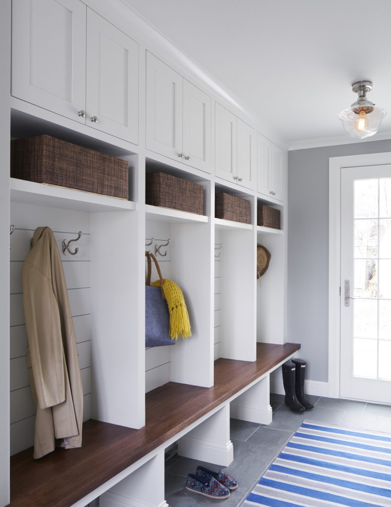The mudroom has cubbies, storage hooks, shelving, and custom cabinetry.