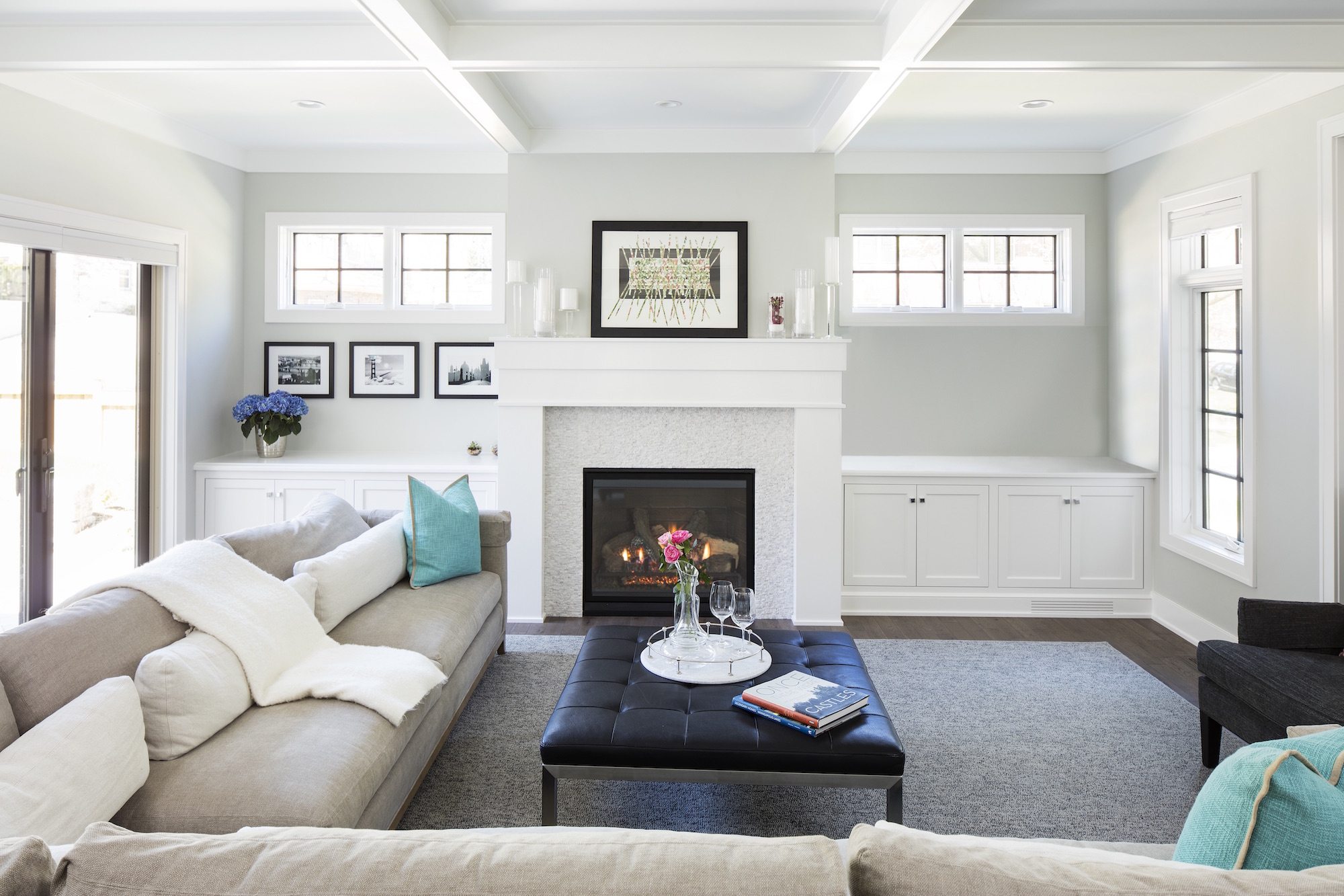 A white enameled coffered ceiling unifies the living space, dining area, and kitchen.