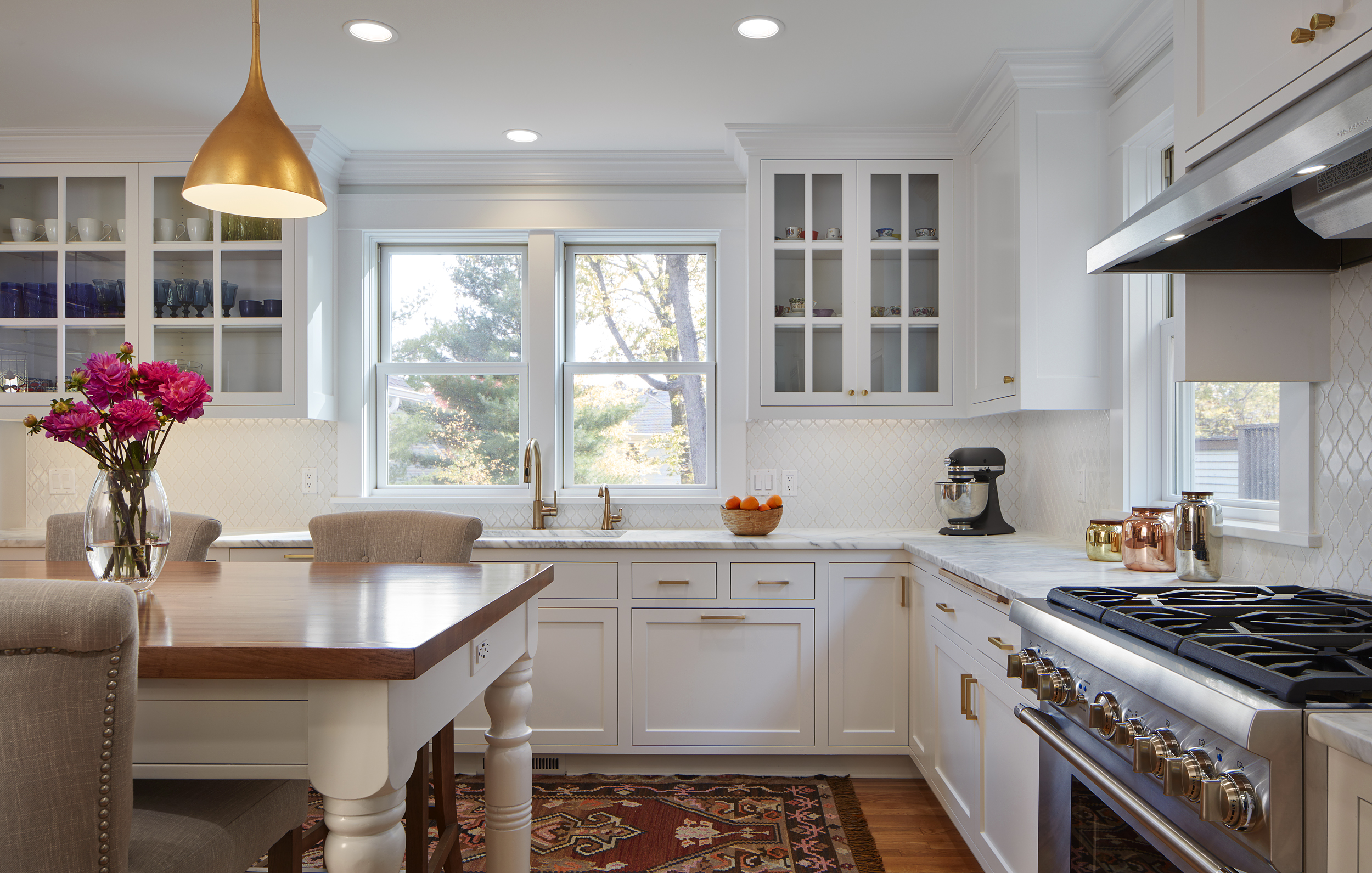 The remodeled kitchen overlooks the large pines on the Lake Harriet hillside.  Some of its features include brass hardware and marble countertops.